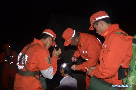 Rescuers treats a wounded villager at Mangla Village of Yongping Township at Jinggu County of Pu'er City, southwest China's Yunnan Province, Oct. 8, 2014.