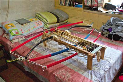 """放在床上的""""诸葛连弩""""。昨日,廖师傅展示自制的诸葛连弩。新京报记者"""