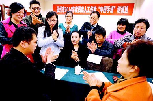 促进残疾人工作者与聋哑人的无障碍交流.图为9日部分残联干部在