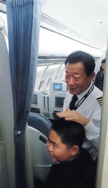 11月10日晚,飞机备降后,机长贺中平微笑着摸着一位男孩的头。网友供图