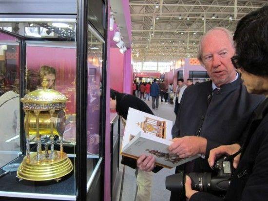 资料图片:美国商人约翰(左)展示法国景泰蓝古董钟表。