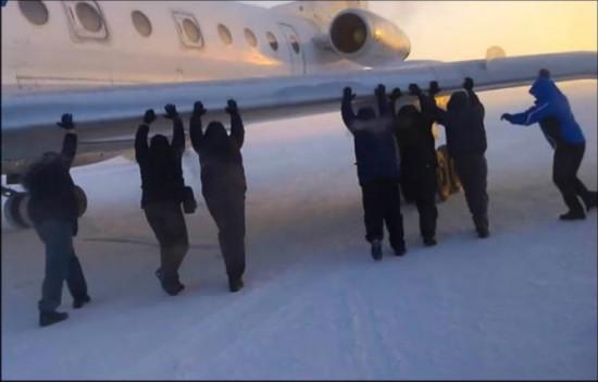 伊加尔市一架客机起飞前被冻在了跑道上。飞机上的乘客不得不下来推飞机。