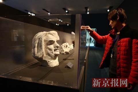 工作人员在给雕塑贴二维码方便观众了解作品
