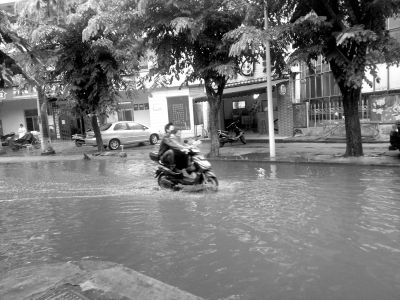 海口:幼儿园门前积水难退 接送孩子得抱着走