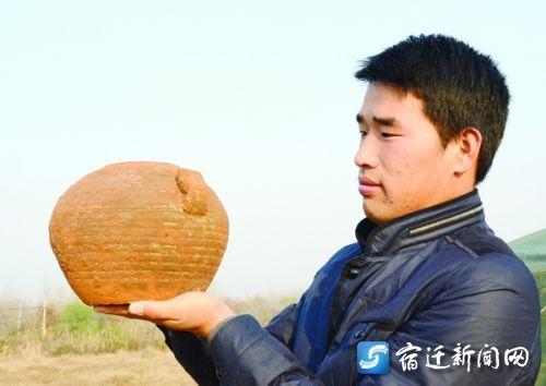 工作人员展示出土的红陶罐。