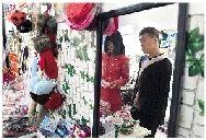 吴建平在自己开的一见钟卿衣舍内向前来选购物品的同学介绍产品。