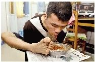 吴建平已经可以熟练地用脚吃饭。