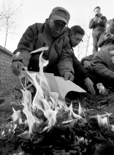 李三仁在儿子坟前焚烧再审无罪判决文书的复印件。新华社发