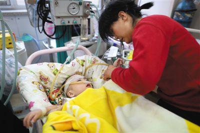 昨日,北京兒童醫院急診樓,媽媽正在照顧患有先天性心臟病的1歲男童舟舟。此前,舟舟被父母遺棄在兒童醫院內21天。新京報記者