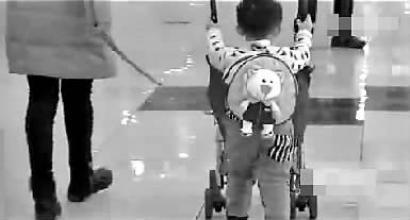 小男孩被家长用绳拽着走视频截图