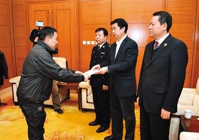 王国强(左)在首都机场向纪检监察机关递交自首书。