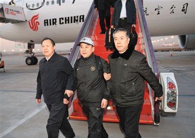 昨日,王国强(中)回国投案自首,到达首都机场。