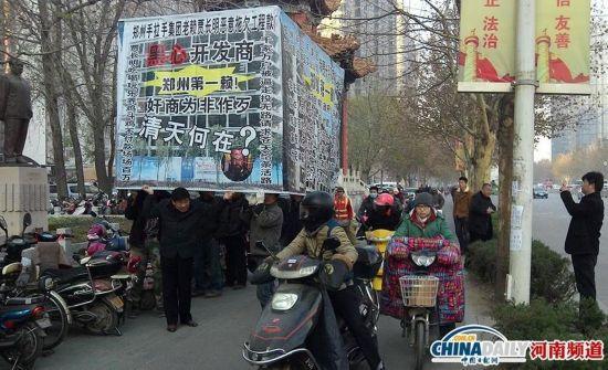 """郑州街头数男子头顶""""自制房子""""讨要工程款"""