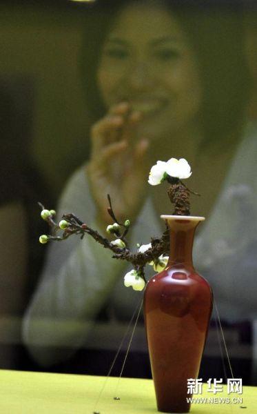 """12月24日,观众在台北故宫博物院欣赏清康熙""""豇豆红瓷柳叶瓶""""。"""