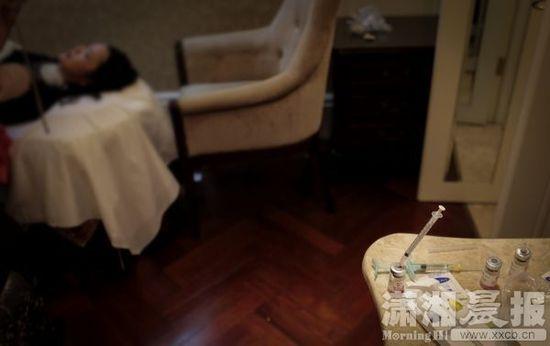 """1月4日,长沙芙蓉区某酒店客房内,一旁的桌上摆放着针管和药剂,一名""""韩国""""医生刚给顾客注射完药剂。图/潇湘晨报记者陈正"""