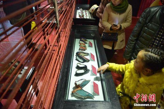 """图为游客在参观。""""三寸金莲""""原是女性小脚的代称,现在也用来称呼她们穿过的弓鞋。""""三寸金莲博物馆""""展览面积1500平方米,所收藏的文物大多来自山东、山西、台湾等地,其时代前溯明朝,晚至现代,最短的弓鞋长度只有9厘米。"""