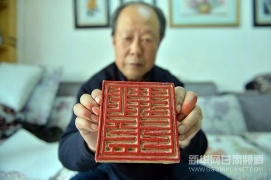 在武威市凉州区家中,孙寿龄展示泥版画模板(1月6日摄).