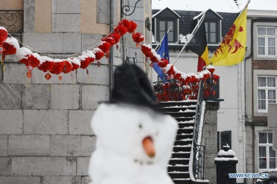 A snowman is seen before the building decorated with Chinese lanterns during the Art Biennale in Theux in eastern Belgium on Jan. 24, 2015.