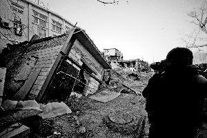一间倒塌在坑内的房屋已经被回填的沙土埋了一半。 张静雅 摄