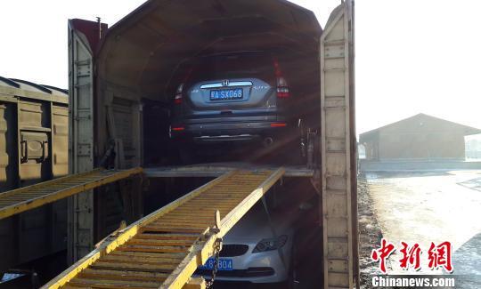 哈尔滨铁路局今起开行黑龙江省首趟赴海南的自驾游小汽车运输快运班列,该列车运行距离超过4000公里,单程运输期限为7天。图为汽车上火车的装运现场。 王栋梁 摄
