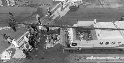 昨日,事发的垃圾箱旁仍围着很多人,而吴老汉的蹊跷死因也在警方的进一步调查之中 新文化记者 张英男 摄