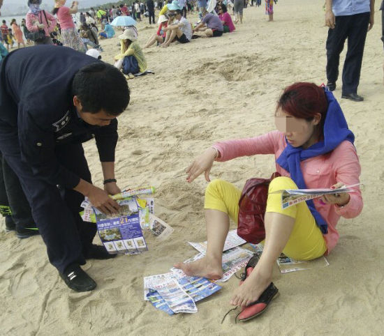 2月3日,三亚市天涯区执法人员在三亚湾海滩上捡拾垃圾。 尹海明 摄