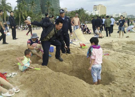2月3日,三亚市天涯区执法人员在三亚湾海滩上劝导游客不要挖深坑时差点摔倒。