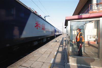 2月10日,位于石景山区的养三站,工作人员注视列车经过。春运期间,一些小站虽无乘客上下车,但仍是保障铁路网线准点运行不可缺少的一环。