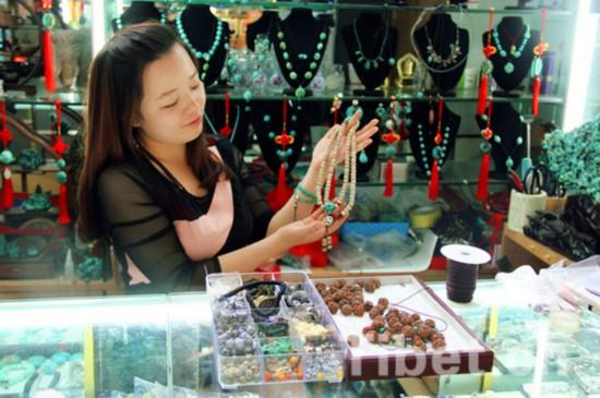 在拉萨民族商城做菩提念珠和手链生意的小娟展示她的最新作品。摄影:杨旭