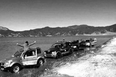 越野车在湖泊的浅滩里,车辆周围的湖水浑浊