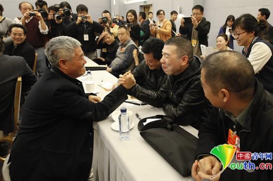 2013年3月7日,全國政協十二屆一次會議,在文藝界小組聯組討論會后,委員們相聚一起親密交流。趙本山委員與電影導演馮小剛委員來了一場掰腕子較量。中國青年網記者張炎良 攝