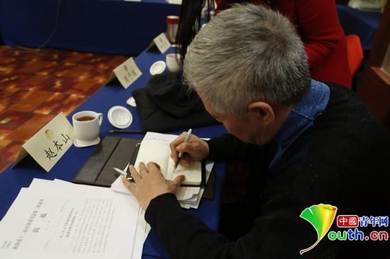 2014年3月5日,趙本山在小組會議間隙為記者簽名。中國青年網記者 張炎良 攝