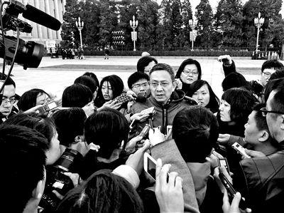 贾康委员被记者团团围住 摄影/本报记者 崔峻