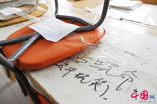 """2015年3月4日,河南省鄭州市,佔座學生將凳子用透明膠帶牢牢粘在桌子上,並放出""""狠話""""。中國網圖片庫 供圖"""