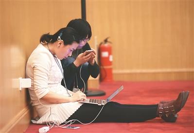 """手机电脑齐上阵 看两会现场""""蛮拼""""的女记者"""