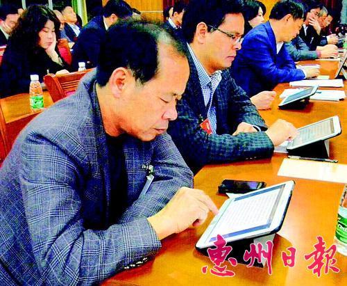 政協委員用平板電腦查看會議文件。