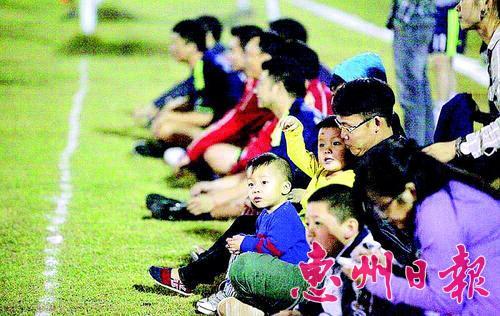 足球爱好者带着孩子来观看比赛。(翻拍)