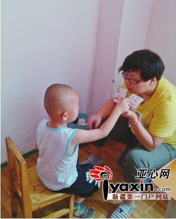 雨虹智障儿童康复中心特教老师周漩在教一名小朋友认字.图片