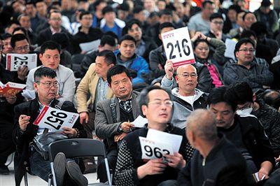 昨日,北京市昌平北七家,亚运村汽车交易市场,中央和国家机关公车改革取消车辆专场拍卖会,一位竞拍者举牌。新京报记者