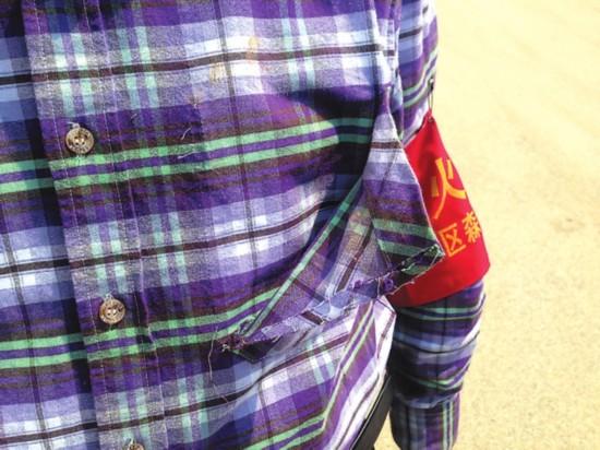 一名防火队员的衬衣口袋被扯破