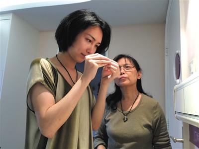 2015年4月6日,广州,完成变性手术的刘婷,在病房内帮母亲穿针,陆永敏为女儿缝补裙子。