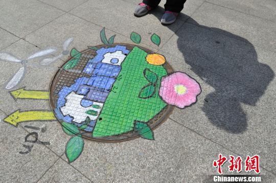 山西大学生绘制环保井盖画迎世界地球日