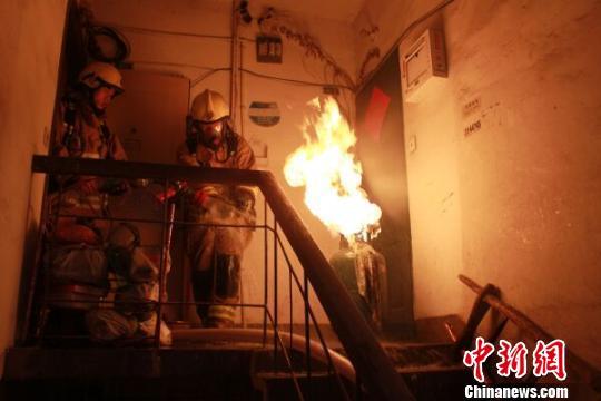 """浙江消防现""""抱火哥""""双手拎出喷火煤气罐(图)"""