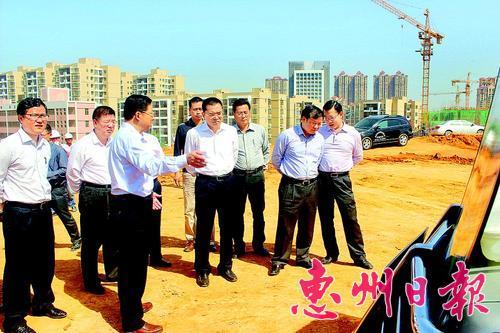 李灿洪(中)听取工程进展汇报。