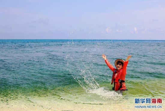一名游客在中国南海西沙群岛鸭公岛的海边戏水(4月22日摄)。