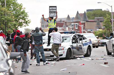 27日,美国巴尔的摩,抗议者摧毁一辆警车。当日,巴尔的摩示威抗议演变为大规模骚乱,当局被迫宣布进入紧急状态。