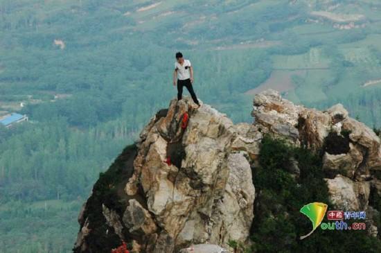 游客不惜危险 河南百米高悬崖绝壁上拍照留影