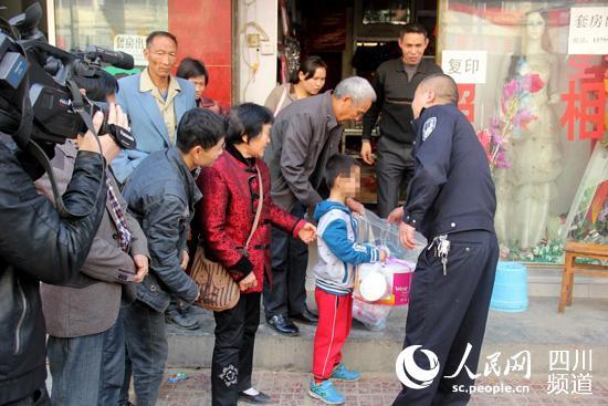 办案民警看望无辜的孩子。(高志农  摄)