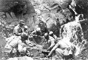 """由于日军的残酷""""扫荡"""",造成了敌后战场严重的困难局面。图为八路军以野菜充饥,露宿山野。"""