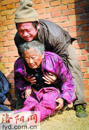 陈相锋将晒太阳的母亲抱起。 图片来源:洛阳网